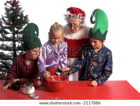 A group of young children aged 6 - 12 wearing elf hats and pj's baking cookies. One boy watching, one boy adding milk and the girl stirring while Mrs Claus looks on