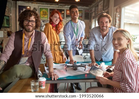 A group of young creative people in a relaxed atmosphere in the office are posing for a photo while enjoying a work on a project together. Employees, office, work