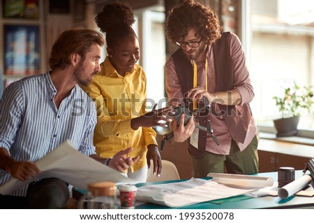 A group of young creative people in a working atmosphere in the office are observing the drone they will use in the project. Employees, office, work