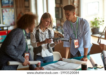A group of young creative people in a working atmosphere in the office observing the drone they will use in the project. Employees, office, work