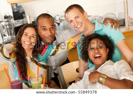 A group of young friends are laughing together while smiling at the camera.  Horizontal shot.