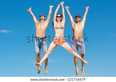a group of young friends jumping on a background of blue sky, having fun