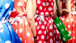 A group of young girls in multi-colored dresses with polka dots. Retro fashion of red and blue dresses with white polka dots. Concept of 50s fashion background.
