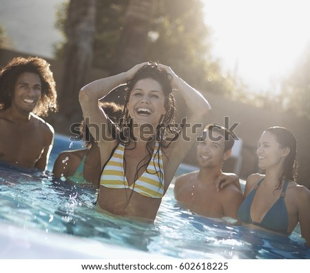 A group of young men and women in the swimming pool at the end of a hot day