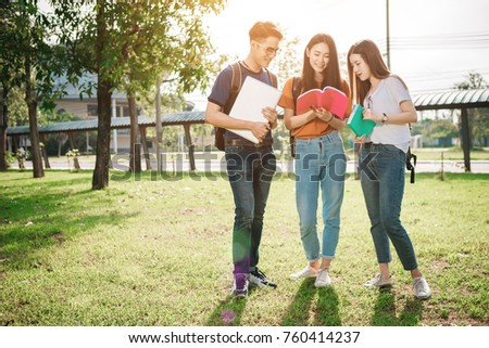 A group of young or teen asian student in university smiling and reading the book and look at the tablet or labtop computer in summer holiday.