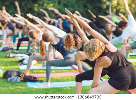 A group of young people do yoga in the Park at sunset. #1306849705