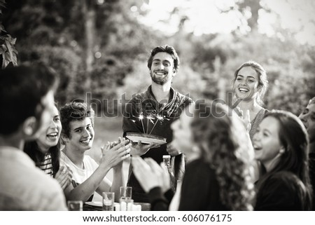 A group of young people gathered on a terrace to celebrate the birthday of one of their friends. A young man holding a cake with candles on it. Black and white picture