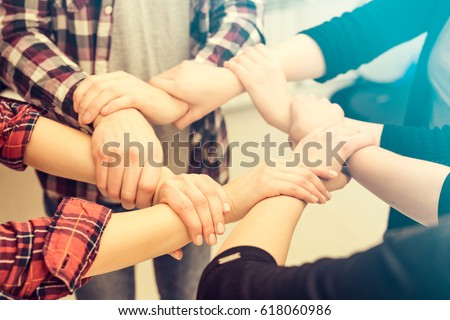 A group of young people hold strong hands. Sign of trust and teamwork.