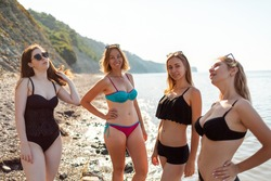 A group of young women with a diverse body shape pose in swimsuits. In the background-the sea and sky.Copy space. Concept of vacation, holiday at the sea and bodypositive