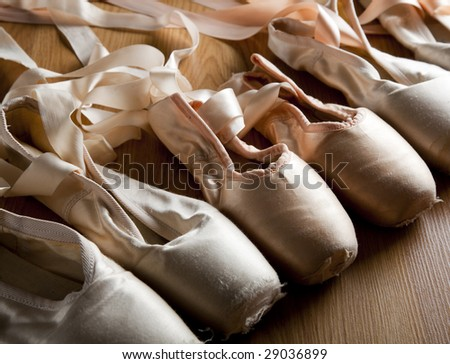 A group or background of used ballet pointe shoes or slippers on a wooden floor