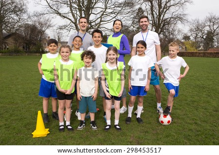 A group portrait of a kids soccer team, behind them are their coaches. They are all smiling and look happy.