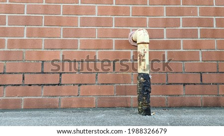 A gruby  dirty yellow gas mains pipe bound with black at the base rising out of a concrete floor turning 90 degrees to enter a brick wall with copy space to the left and a cigarette but at the base. Zdjęcia stock ©