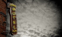 A Grungy Old Neon Motel Sign Against A Stormy Sky With Copy Space
