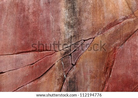 A grungy red laterite stone wall with cracks and stain for textural background.