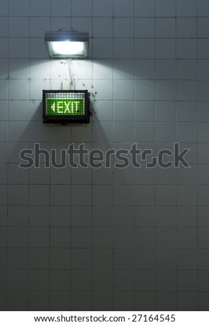A grungy subway exit sign on a tiled wall