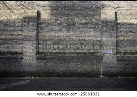 A grungy wall in Cambridge (uk) with moss and litter