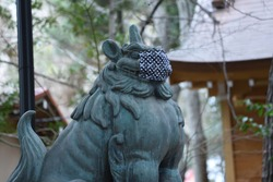 A guardian dog of a shrine wearing a mask for preventing new corona infection.