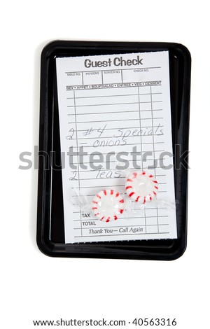A guest check on a tip tray with mints on a white background