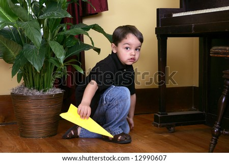 a guilty looking young child holding a yellow paper airplane