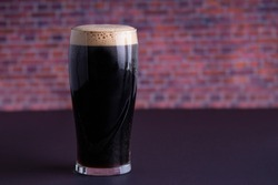 A Guinness dark Irish dry stout beer glass that originated in the brewery in dublin horizontal view