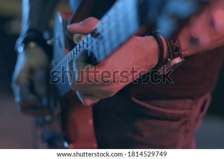 A guitarist plays a rock riff with his guitar on the stage Stock foto ©
