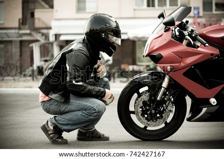 a guy a motorcyclist in a helmet and a leather jacket and jeans sits opposite a motorcycle of a sports red color and look at him face to face