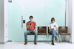 A guy and a girl in medical masks, sitting in a queue, and waiting for a doctor's appointment in the hospital.