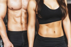 a guy and a girl in the gym doing sports . training