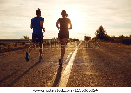 A guy and a girl jog along the road  in nature.  #1135865024
