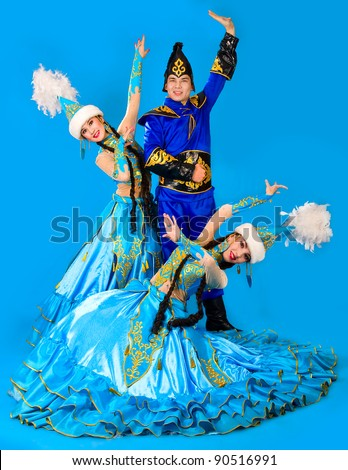A guy and two girls in the Kazakh national costumes