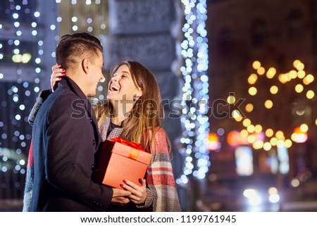 A guy gives a gift to a girl at night on a city street.