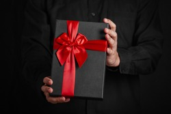 A guy in a black shirt is holding a gift with a red ribbon. Black background. Black gift box in hands. Close-up photo.