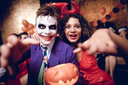 A guy in a Joker costume and a girl in a demon costume posing with a pumpkin-lamp. Behind them sit their friends and relax