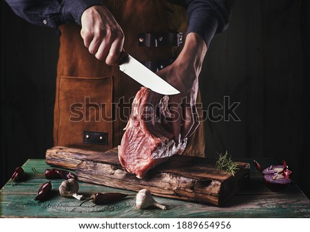 A guy in a leather apron is slicing raw meat. The butcher cuts the pork ribs. Meat with bone on a wooden cutting board.