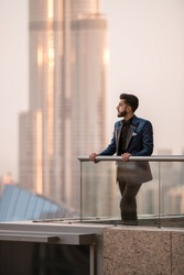 A guy in fancy suit enjoying city views. Iconic Dubai landmark in the background. Golden sunset colors. Luxury travel.
