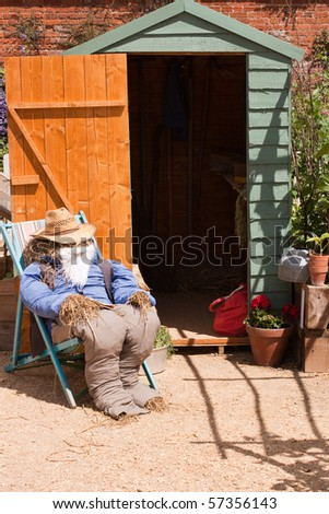 A guy made of straw and old clothing sitting on a deckchair outside of the garden shed
