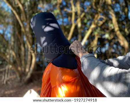 A guy PACK A SLEEPING BAG to fit back into its stuff sack can seem like a magic trick. The perfect way it was packaged at the factory appears impossible to recreate without splitting seams Foto stock ©