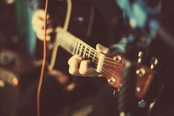 A guy playing an acoustic guitar. Fragment. Focus on the hand
