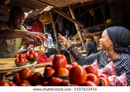 a guy selling tomatoes to a girl in a typical local african market