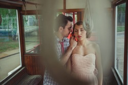 A guy shows his feelings for a girl in vintage clothes inside an old Soviet tram