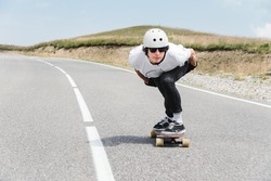 A guy wearing a helmet and sunglasses is riding his longboard on a country road