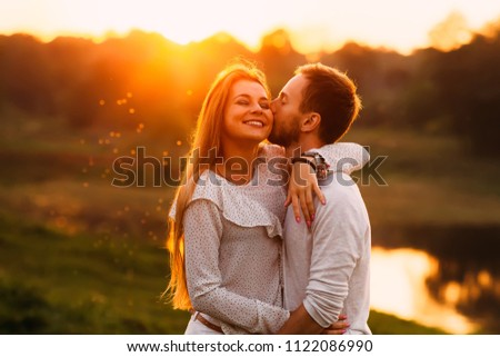 A guy with a beard gently kisses his girlfriend on a cheek and she is enjoying it. gentle hugs on the background of the sunset #1122086990