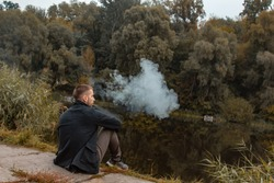 A guy with a beard sits on the lake and smokes an electronic cigarette. Blows puffs of smoke. The concept of unity with nature. Rest near the water. Vape, Man Vaping.