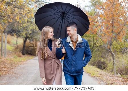 a guy with a girl go under umbrella rain #797739403