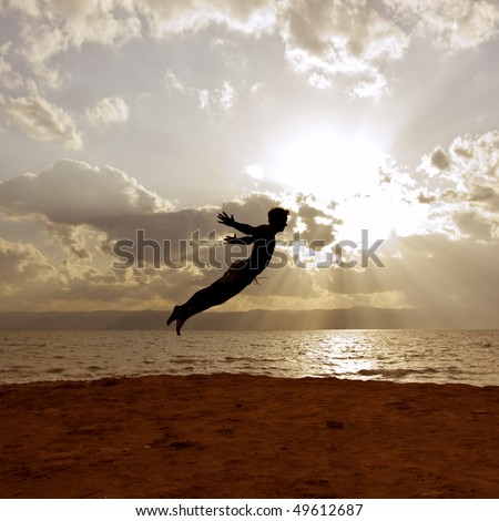 "a guy with Dead-Sea-mud on his skin perform jumping scene in front of the dead sea in jordan. ""Over the sea, some Miles beyond the mountains is Jerusalem""."