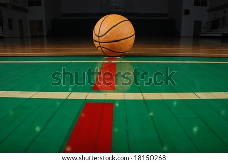A gymnasium\'s shiny floor and leather basketball.