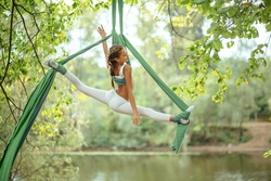 A gymnast in a white suit on aerial canvases performs an acrobatic element over the river against the background of the forest