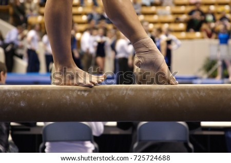 a gymnast points toe on beam during competition.