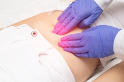 A gynecologist doctor probes the lower abdomen of a girl who has pain and inflammation of the reproductive system. Ovarian cyst, endometriosis, pregnancy pathology