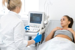 A gynecologist sets up an ultrasound machine to diagnose a patient who is lying on a couch. A transvaginal ultrasound scanner of the internal organs of the pelvis. Female health concept.